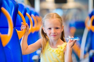 Adorable little girl traveling on train and having fun with airplane model in hands