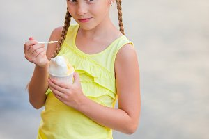 Adorable little girl eating ice-cream outdoors at summer. Cute kid enjoying real italian gelato near Gelateria in Rome