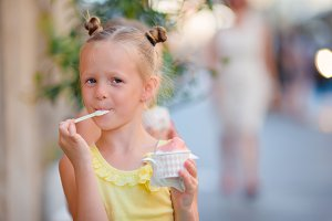 Little girl eating ice-cream outdoors at summer. Cute kid enjoying real italian gelato near Gelateria in Rome