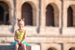 Adorable little girl background of Colosseum in Rome, Italy. Kid spending holiday in Europe