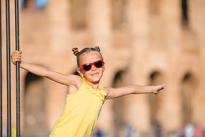 Adorable little active girl having fun in front of Colosseum in Rome, Italy. Kid spending childhood in Europe