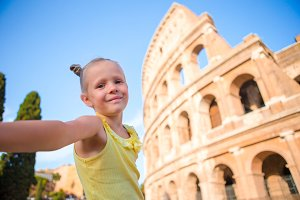 Little girl taking selfie in front of Colosseum in Rome, Italy.