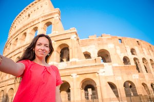 Young woman taking selfie portrait in front of Colosseum in Rome, Italy