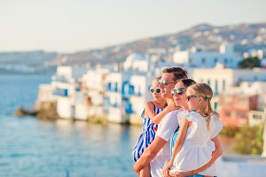 Family in Europe. Parents and kids on Little Venice background on Mykonos Island, in Greece