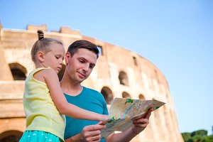 Family with map in front of Colosseum. Father and girl searching the attraction background the famous area in Rome