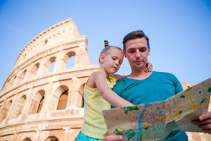 Family with map in front of Colosseum. Father and girl searching the attraction background the famous area in Rome, Italy