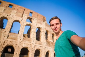 Young man taking selfie portrait in front of Colosseum in Rome, Italy