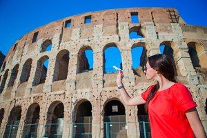 Young beautiful woman with small toy model airplane background Colosseum in Rome, Italy