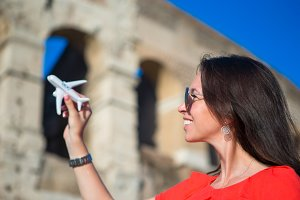Young girl with small toy model airplane background Colosseum in Rome, Italy