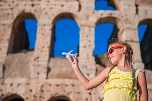 Tourist girl with small toy model airplane background Colosseum in Rome, Italy