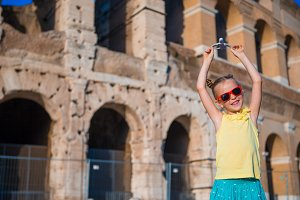 Girl with small toy model airplane on Colosseo background in Rome, Italy