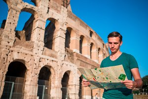 Boy with map in front of Colosseum. Young man searching the attraction background the famous area in Rome, Italy