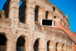 Closeup cell phone in front of Colosseum in Rome, Italy