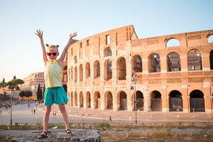 Adorable little active girl having fun in front of Colosseum in Rome, Italy.