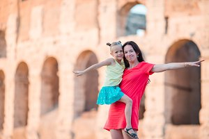 Young mother and little girl exploring Coliseum outside in Rome, Italy. Family portrait at famous places in Europe
