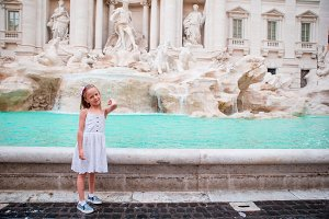 Adorable little girl at Fountain of Trevi in Rome. Happy kid enjoy her european vacation in Italy