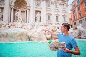 Happy man looking at touristic citymap near Trevi Fountain, Rome, Italy.