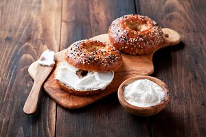 Whole grain bagels with cream cheese on wooden board