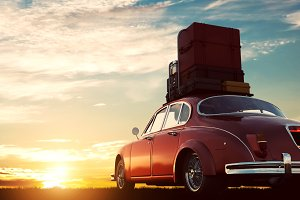 Retro red car with luggage on roof rack at sunset. Travel, vacation concepts.