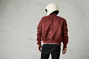 Man in a bordeaux pilot jacket with helmet