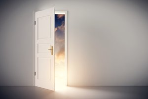 Sun shining through half open classic white door.