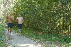 Two young muscular athletes running at the forest path. Active strong men training outdoors. Fit handsome athletic male sportsmans working out. Friends training and exercising. Healthy lifestyle