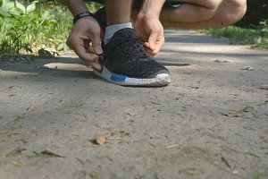 Active fit man tying shoe in the park. Athlete tying shoelaces before jogging during workout training on country route. Feet of strong man running at the forest path. Exercising at a forest. Close up