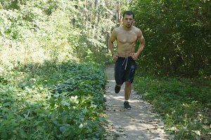 Young muscular athlete running at the forest path. Active strong man training outdoors. Fit handsome athletic male sportsmen working out. Guy training and exercising. Healthy lifestyle. Close up