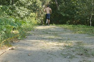 Young muscular athlete running at the forest path. Active strong man training outdoors. Fit handsome athletic male sportsmen working out. Guy training and exercising. Healthy lifestyle. Rear back view