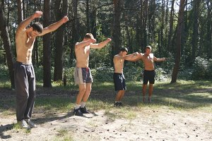 Group of athletes warming up his body and hands before training in the forest. Young strong muscular men stretches before workout at the nature. Sportsmans doing exercise at the wood outdoor. Close up