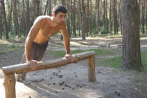 Athletic man doing push ups from log at the forest. Strong young muscular guy training outdoor at the wood in summer. Athlete exercising at beautiful nature. Workout healthy lifestyle. Close up