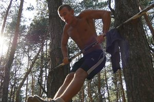Athletic man doing push ups on horizontal bars at the forest. Strong young muscular guy training in the wood in summer. Athlete exercising outdoor. Workout sport healthy lifestyle. Close up
