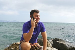 Young smiling man is talking on mobile phone on the beach in the sea. Handsome happy guy sitting on stone near the ocean and speaking on a cellphone with beautiful landscape background. Close-up