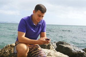 Young man is sitting on a stone and using smartphone near the sea. Portrait of handsome guy with mobile phone at the ocean beach. Boy looking at phone app. He texting sms or chatting in social network