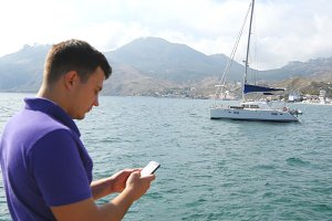 Young man standing near the sea and using smartphone. Yacht in the sea at background. Portrait of handsome guy with mobile phone at ocean beach. He texting sms or chatting in social network. Close up