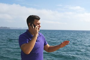 Young handsome man is talking on mobile phone on a sea beach. Serious guy speaking on the cellphone on the background of the ocean. Call from the summer vacation. Beautiful landscape. Close up