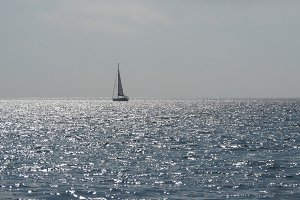 Yacht with sails in calm blue water of sea. Sailboat on horizon in the beautiful landscape. Sailing boat. Yacht sailing on opened ocean. Yachting at windy day.