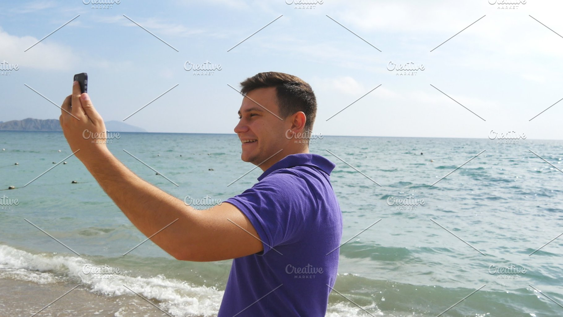 Young smiling man having a video call on smart phone at the sea beach   Happy guy making video online chats on beautiful landscape background  Boy