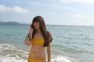 Young attractive woman in a swimsuit is talking on mobile phone on a sea beach. Serious girl in bikini speaking on the cellphone on the background of the ocean. Call from the summer vacation. Close up