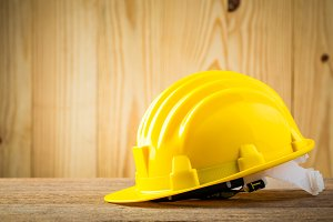 Safety helmet on wood background