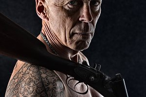 Tough tattooed man with a shotgun