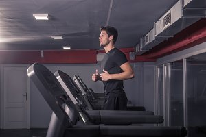 fit slim young man running treadmill