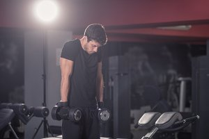 young man arms high dumbbells gym