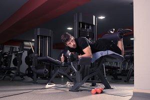 young man leg curl gym utility bench