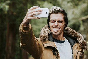 boy with mobile phone becoming a selfi outdoor