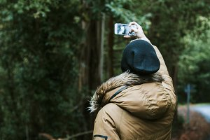 boy making a selfie photo in the forest