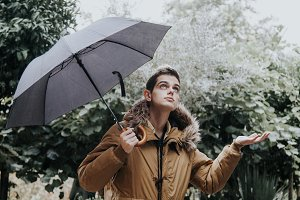 young man with umbrella on rainy day