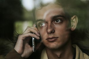 young man talking on the phone behind the window