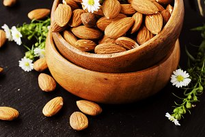 raw almonds in a wooden bowl selective focus
