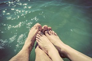 A couple in love wetting their feet in the sea. Summer holidays. Vintage.